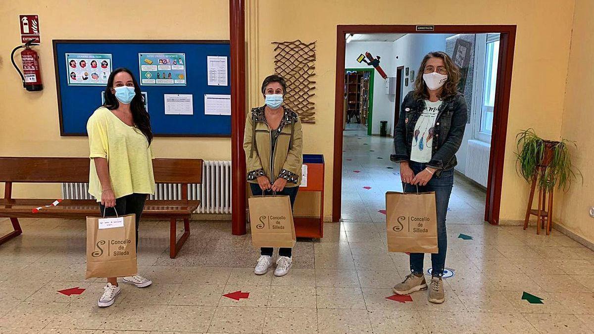 Troitiño y González, durante la entrega de material en el colegio de A Bandeira. A la derecha, Cuiña en su videoconferencia.