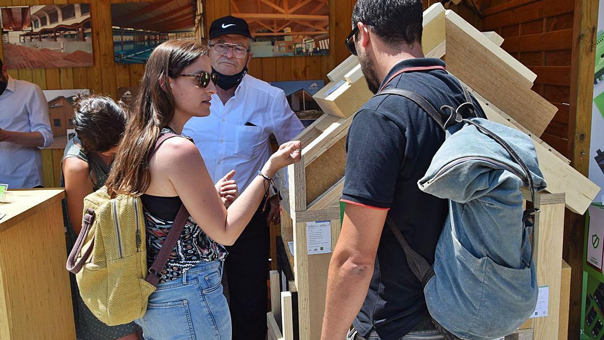 Un expositor, atent a les impressions d'assistents a la fira sobre un element | GUILLEM CAMPS