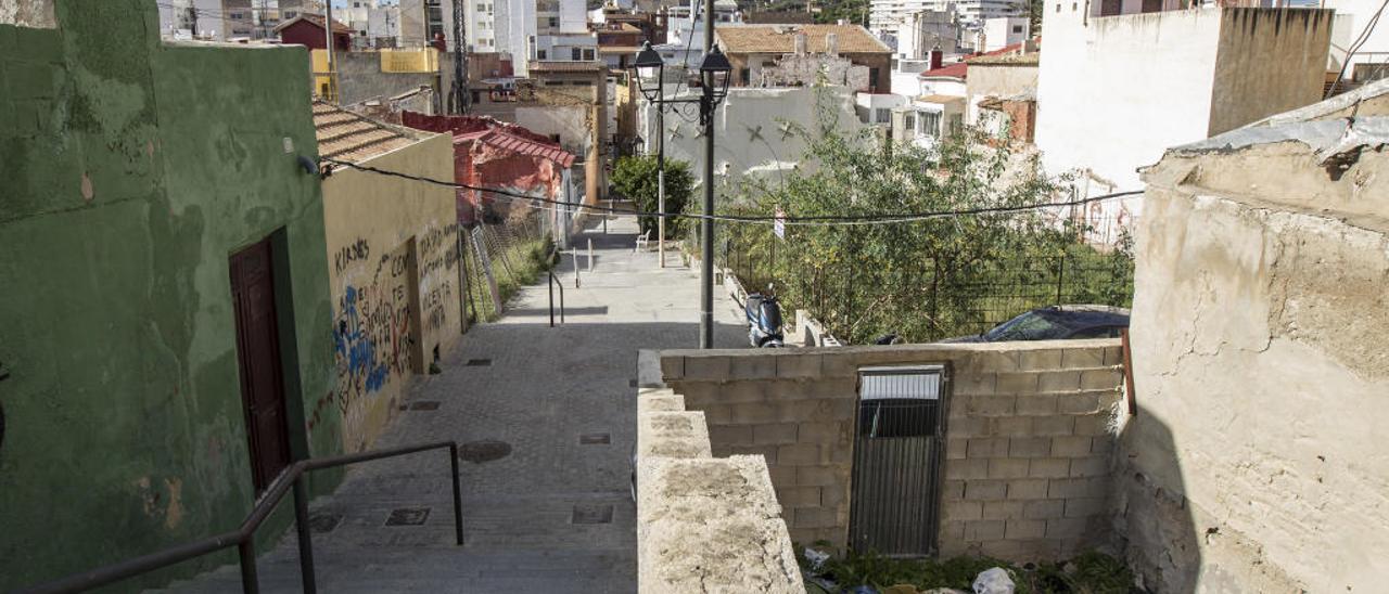 Una de las calles del barrio, con pintadas en las paredes y un solar lleno de desechos.