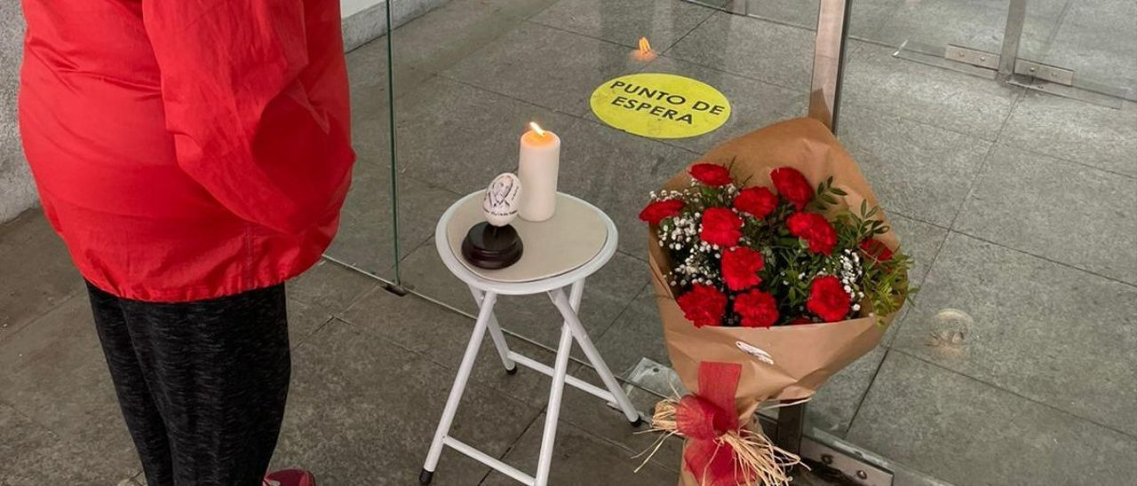 Una mujer lee la esquela de Amador  junto a su puesto de siempre, donde se depositaron flores y velas en su recuerdo.