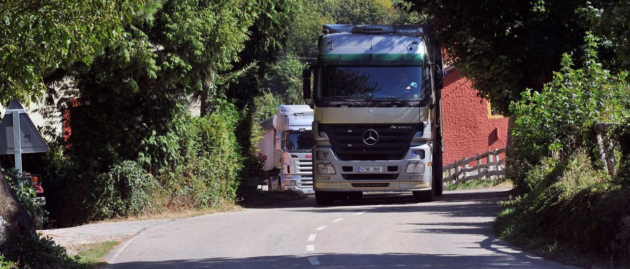 Dos camiones circulan por la carretera de Tarna, a la altura del pueblo de Bezanes.