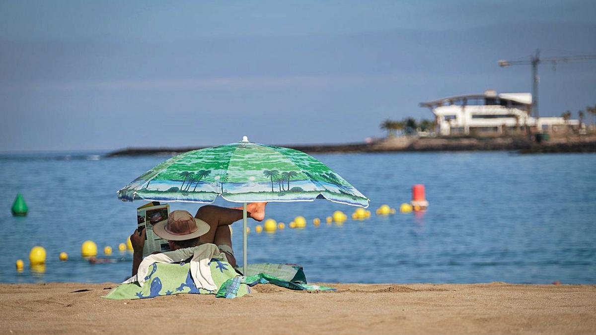 Un turista en la playa de Las Vistas de Los Cristianos, en el municipio de Arona. | | ANDRÉS GUTIÉRREZ