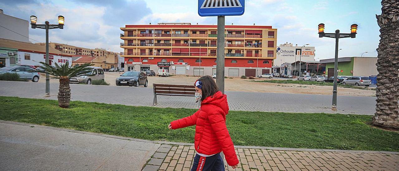 Una niña «cruza» por delante de una de las señales con la silueta de una menor.  | TONY SEVILLA