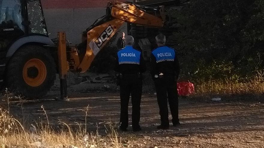 Dos agentes de la Policía supervisan unas obras de derribo