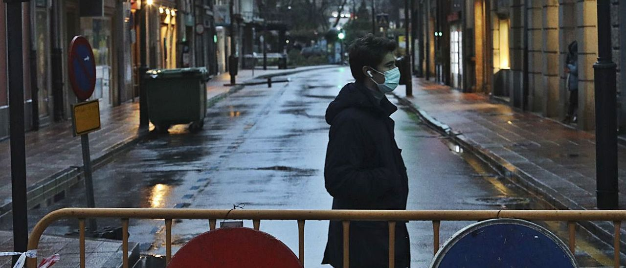 Un joven cruza, ayer, por la calle La Muralla, cortada ya al tráfico. | Ricardo Solís