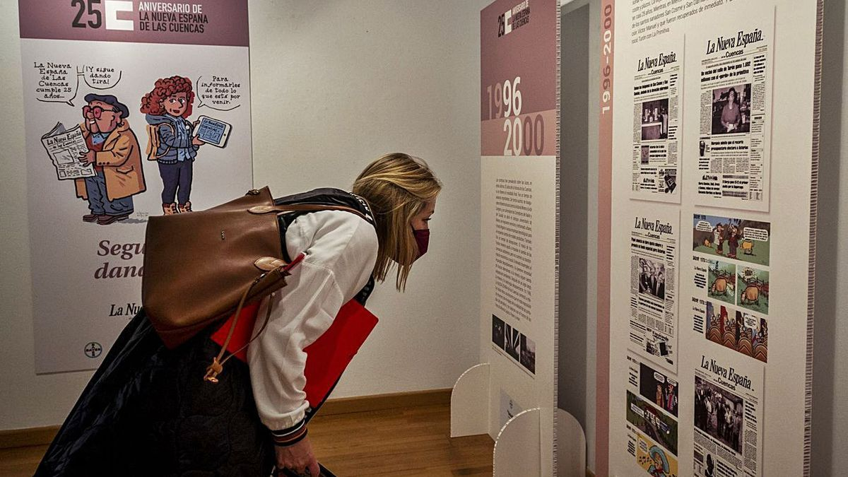 Arriba, Lucrecia Fernández contempla varias de las portadas de la muestra. A la izquierda, Álvaro Fernández, en la exposición. | Nazaret Quintas