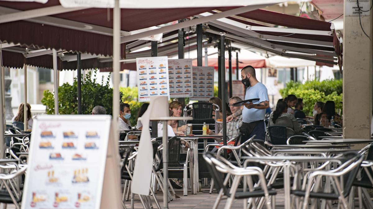 Un camarero atiende una mesa en la terraza de una cafetería.