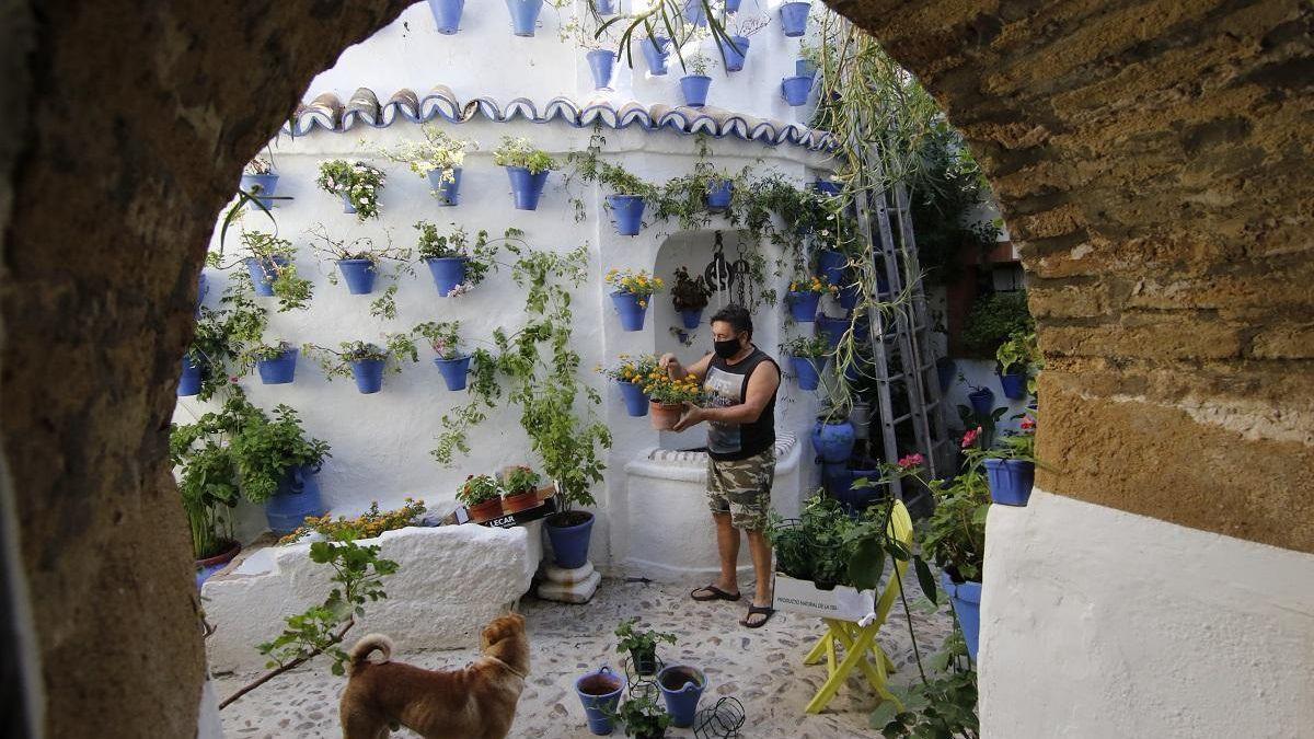 Un cuidador prepara una maceta en un bello patio de Córdoba.
