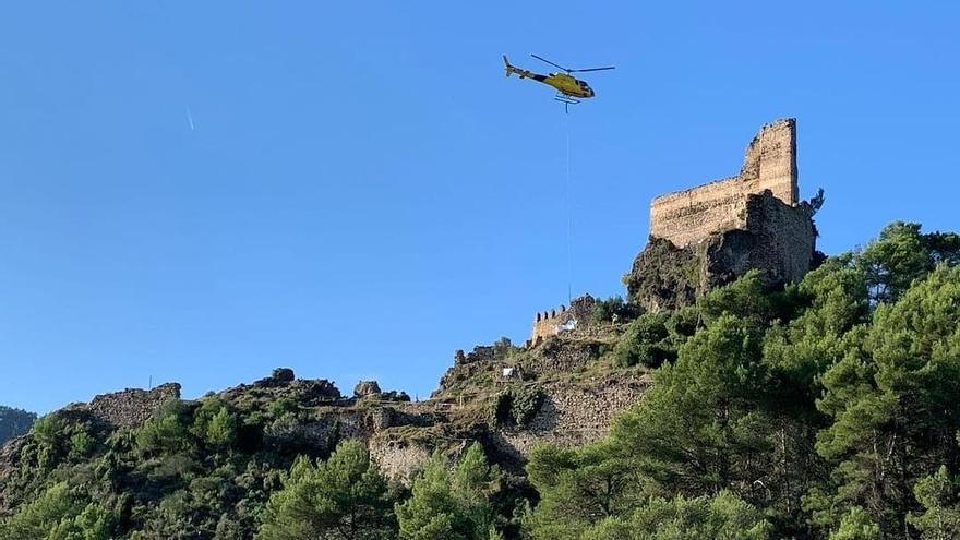 Un helicóptero transporta desde el aire los materiales de obra para restaurar el castillo de Suera