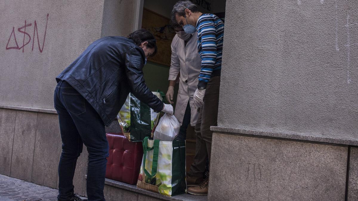 """Un joven recoge el menú diario ofrecido por el centro """"Madre Bonifacia"""""""