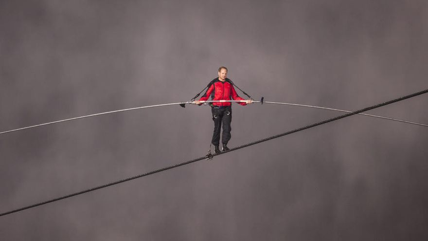 Un acróbata cruza en un cable el lago de lava de un volcán