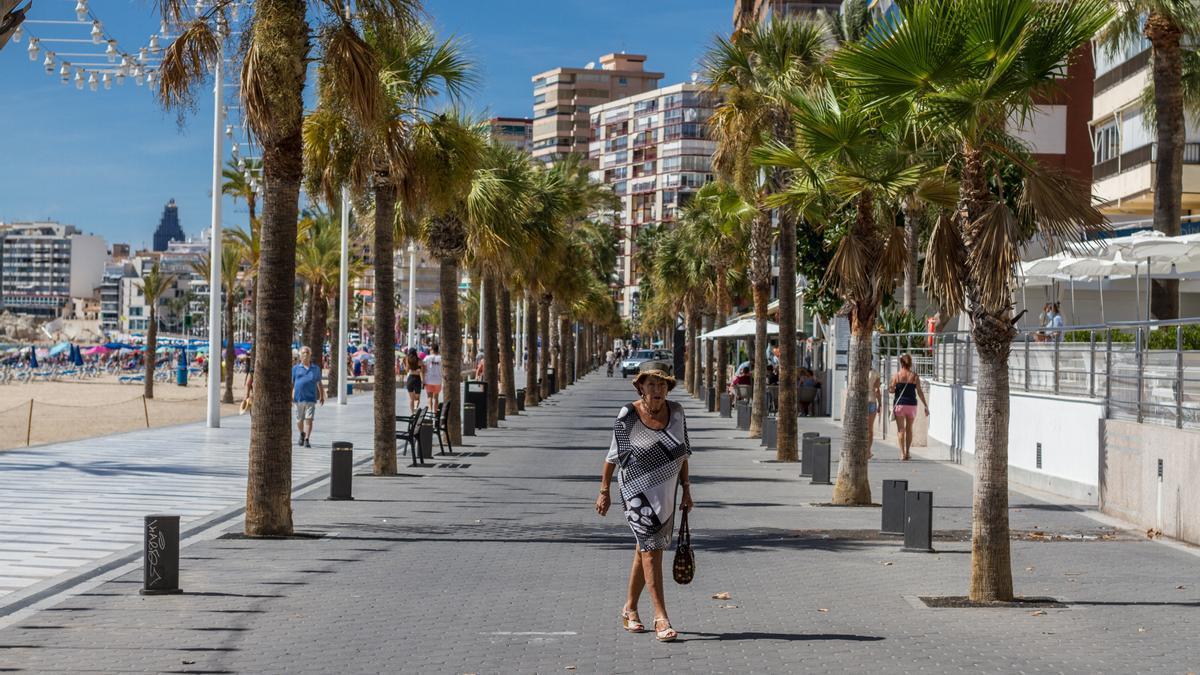 Archivo - Una mujer pasea por el paseo marítimo de Benidorm durante el Día Mundial del Turismo 2020