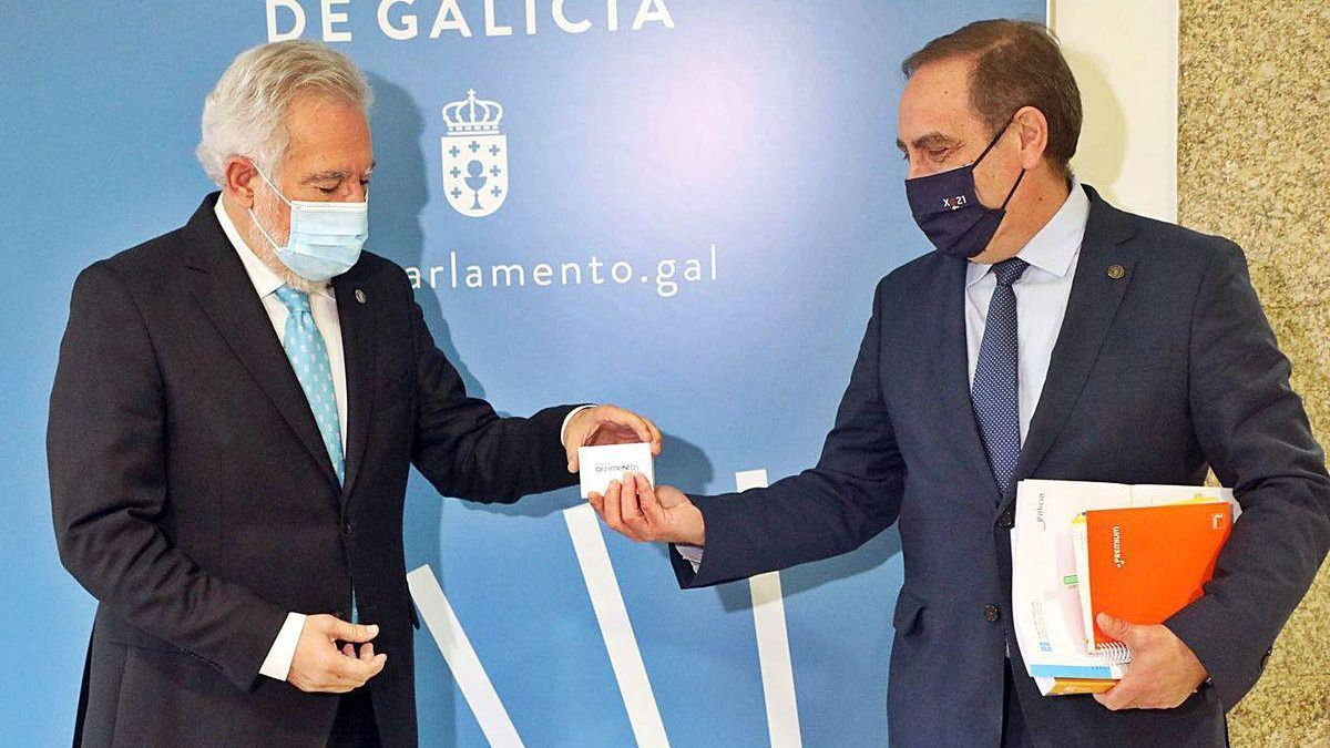 Miguel Santalices recibe de manos del conselleiro de Facenda el proyecto de presupuestos.