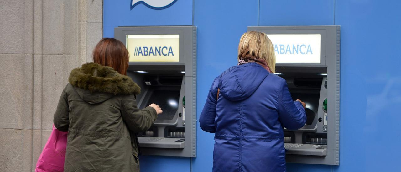 Dos mujeres sacando dinero en una sucursal de Abanca. // Gustavo Santos