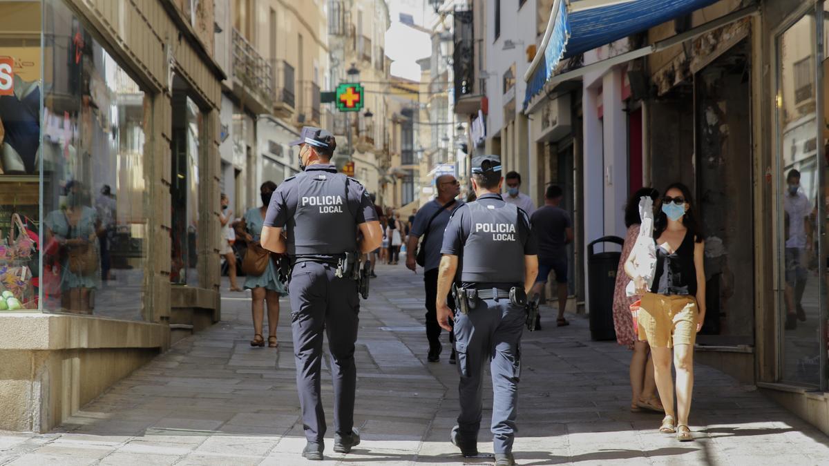 Dos agentes de la Policía Local de Cáceres patrullan por la calle Pintores.