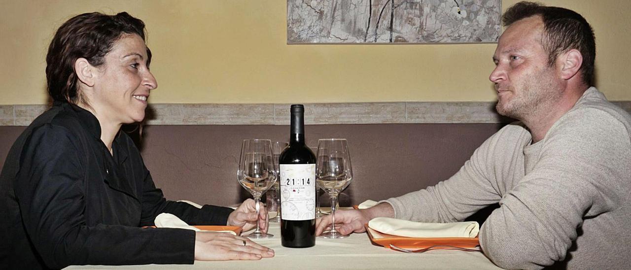 Laura Adrover y David  González, propietarios de  Sa Cuina de n'Aina, con su vino 21:14.