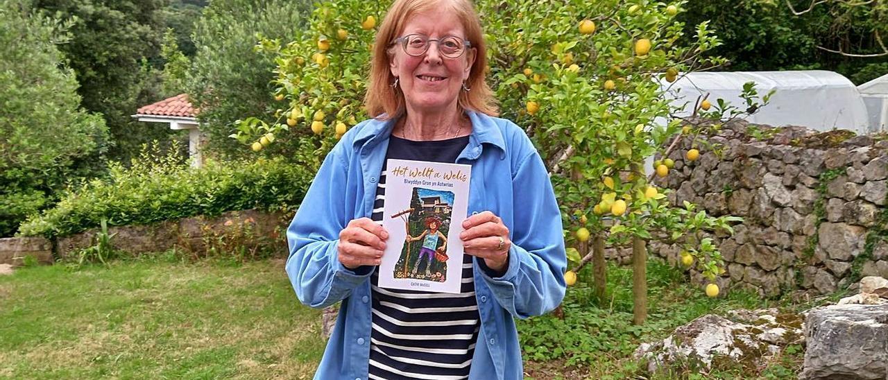 Cathi McGill, en su huerta de Cuerres (Ribadesella), con un ejemplar de su libro sobre Asturias.   María Villoria