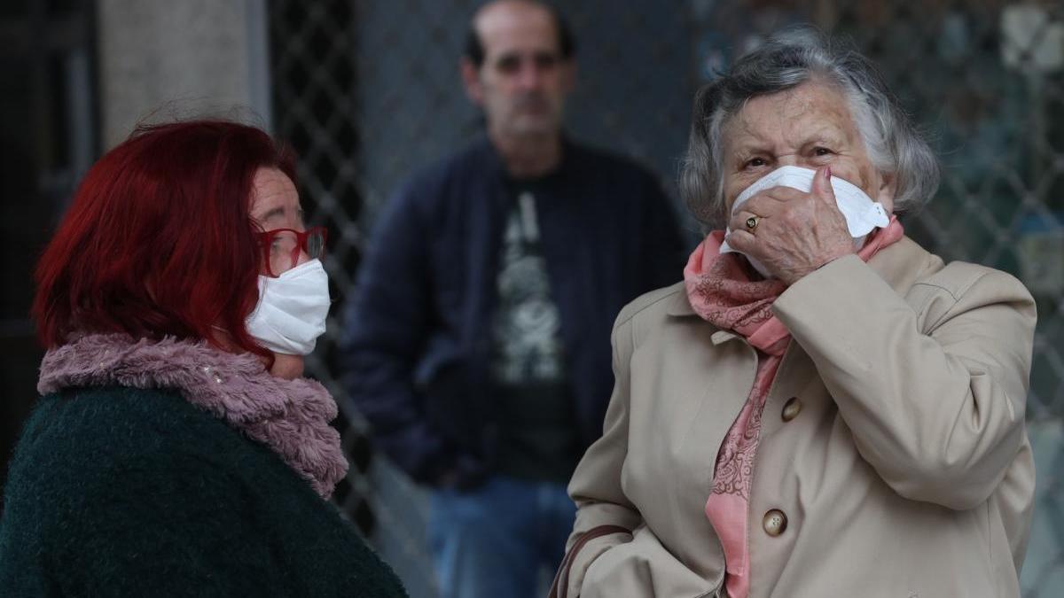 Una mujer mayor haciendo cola para entrar en un establecimiento durante el estado de alarma. // Ricardo Grobas