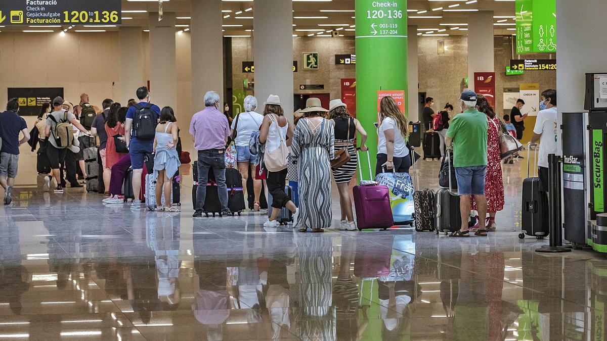 Pasajeros en el aeropuerto de Palma esperan para facturar.