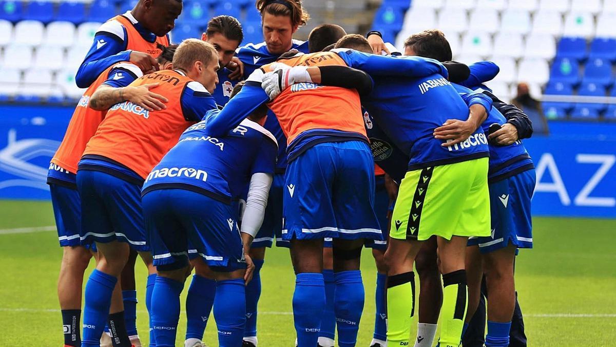 Los futbolistas del Deportivo, abrazados, hacen piña sobre el césped de Riazor.