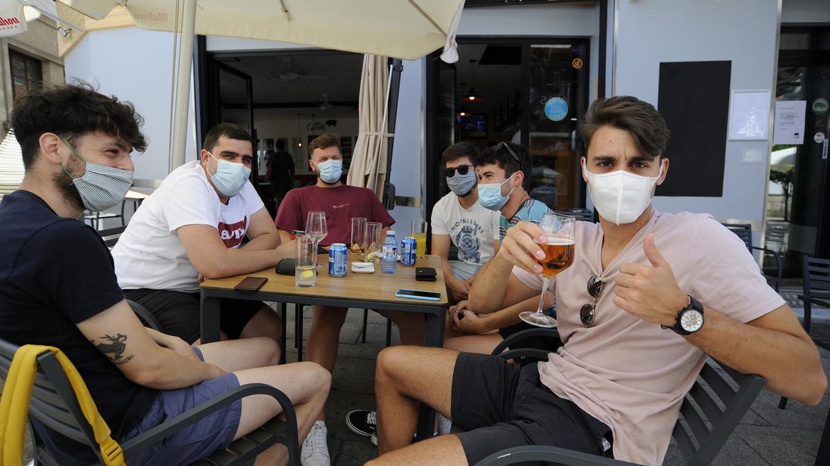 Jóvenes disfrutan de unas bebidas en una terraza de Lalín