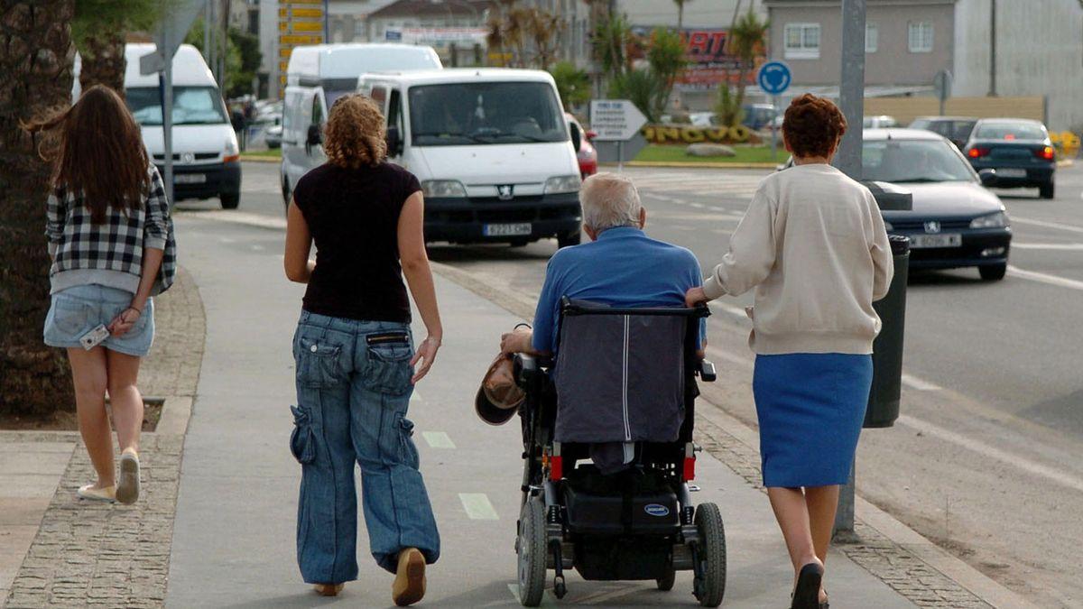 Un persona mayor dependiente pasea en silla de ruedas con sus familiares.