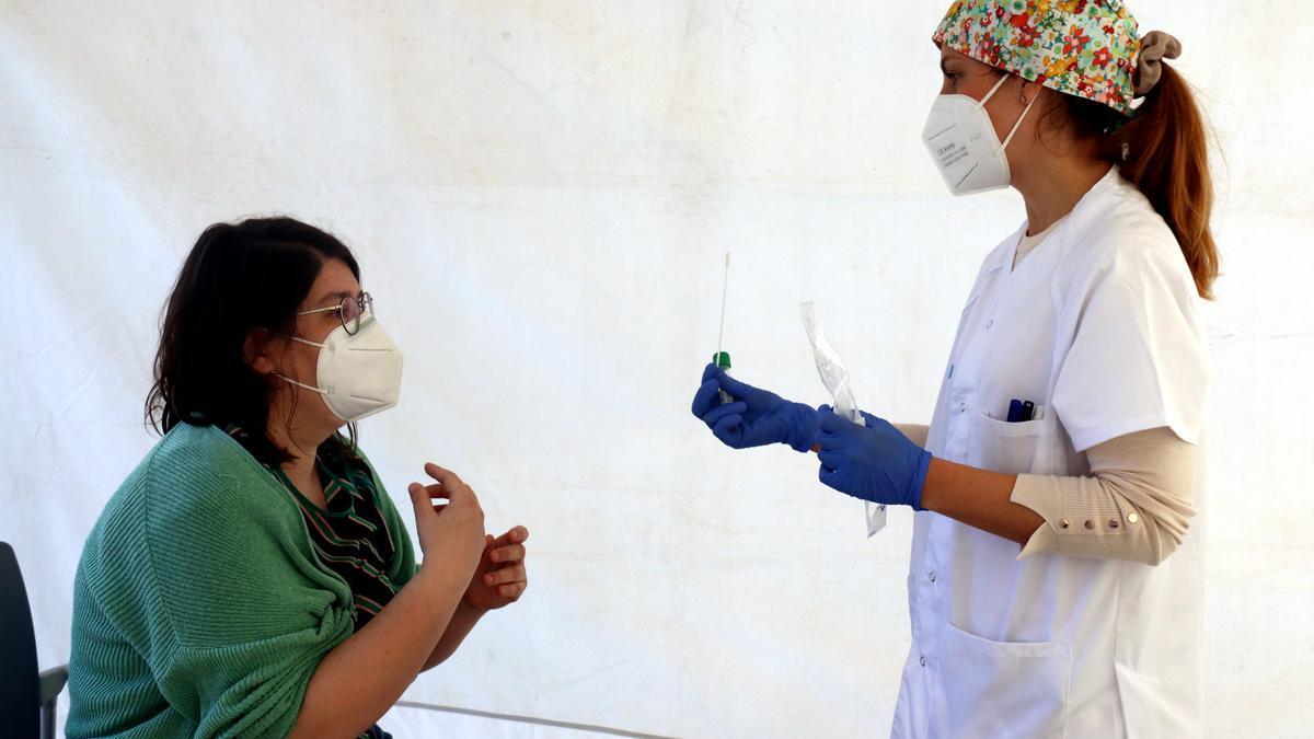 Una infermera del CAP d'Artés entrega el kit automostra a una veïna de la població