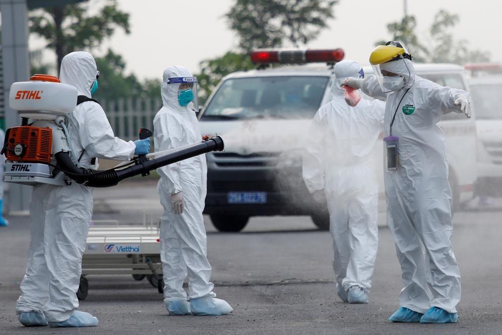 Sanitaris es ruixen un desinfectant després de tractar amb obrers vietnamites infectats amb la Covid-19