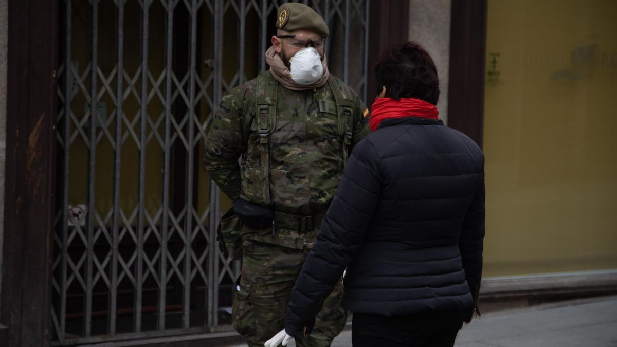 Un militar atiende las preguntas de una mujer en la calle.