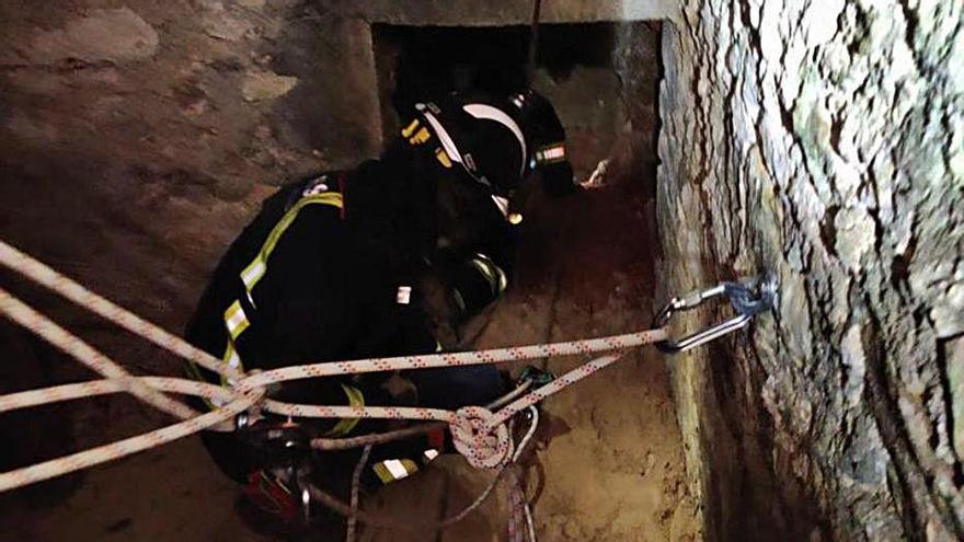 A la izquierda, el bombero en el interior del pozo llevando a cabo el rescate; a la derecha, con el perro rescatado.   BOMBEROS