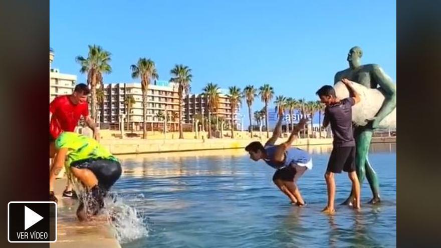 Saltan a la escultura del surfista en el Puerto de Alicante para subirlo a Tik-Tok y acaban en el agua