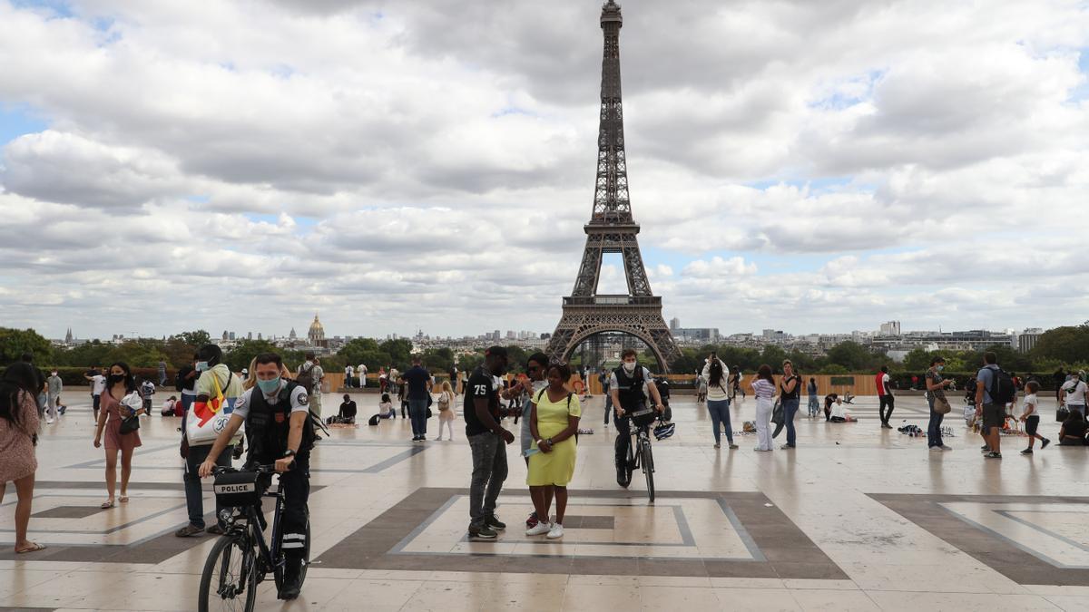Ciudadanos pasean frente a la Torre Eiffel.