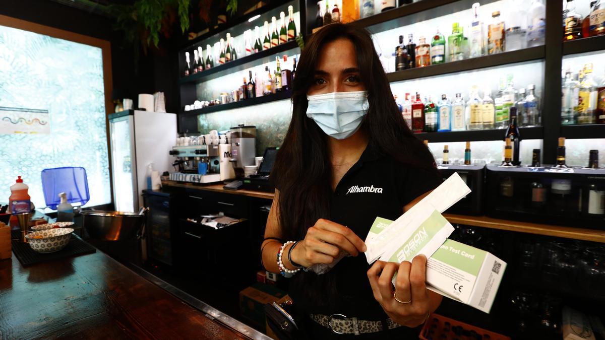 Una camarera del Bocachica muestra los test que están a disposición de los trabajadores