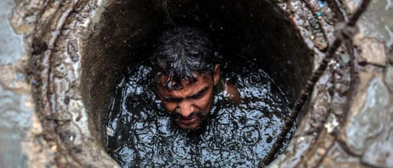 Un hombre  limpiando una fosa séptica en la India.