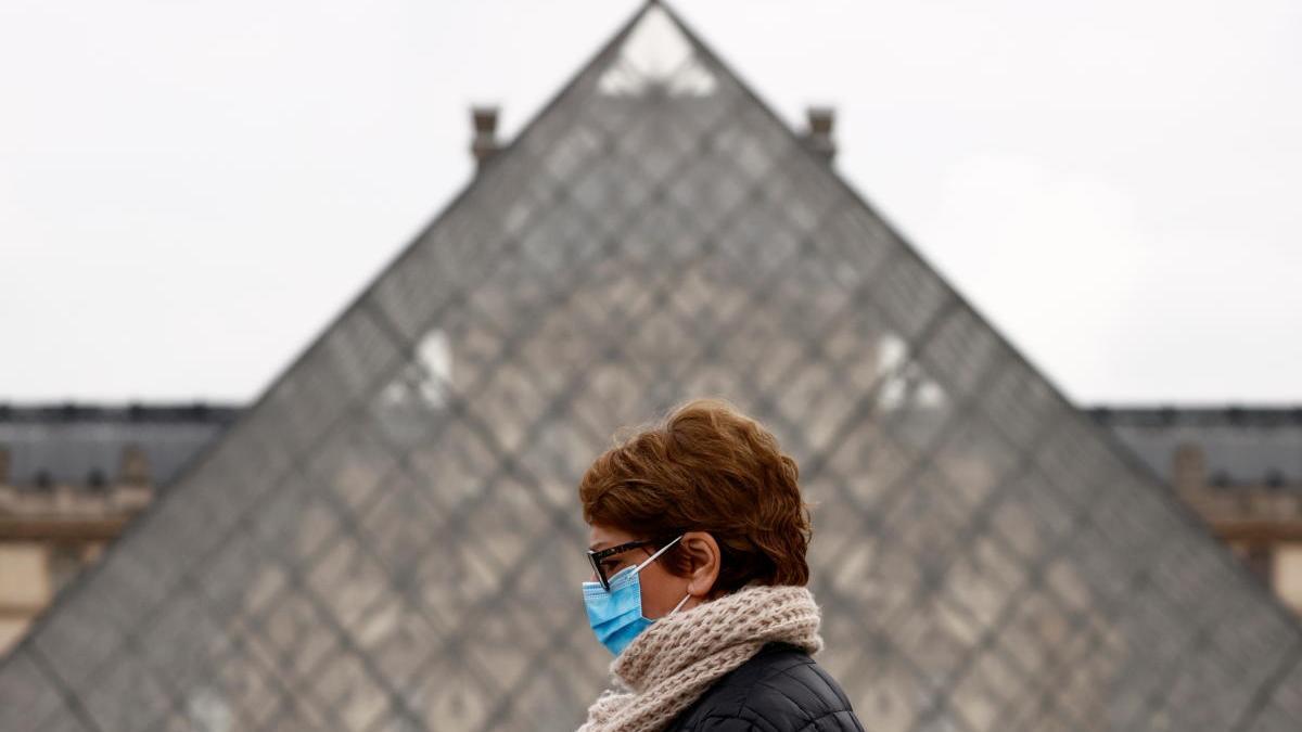 Una mujer con mascarilla pasa frente a la pirámide del Louvre, en París