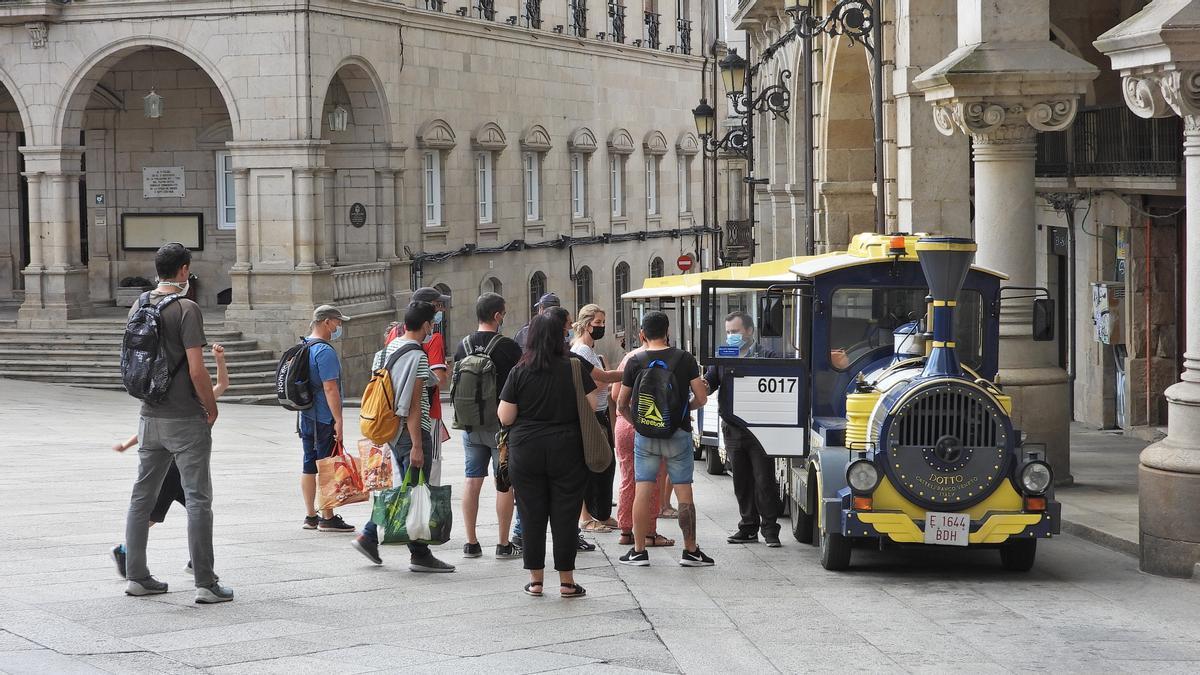 Turistas ante el tren turístico de Ourense.
