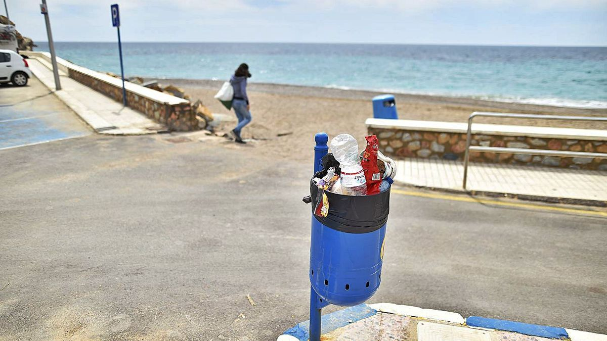 Las papeleras de la playa de El Portús, a rebosar tras el fin de semana. | URQUÍZAR