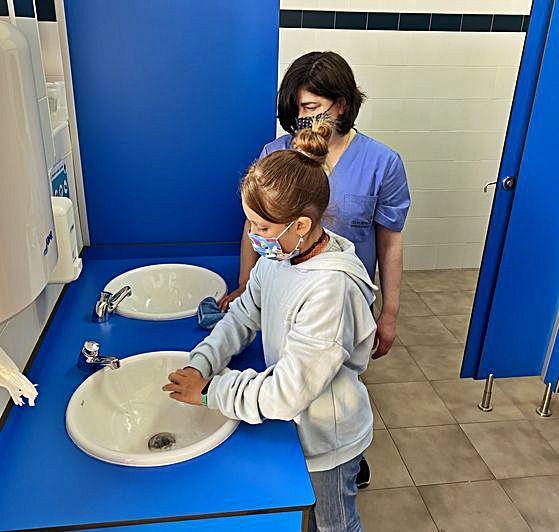 Sara Carbajal se lava las manos ante la mirada de María Antonia Silgado.