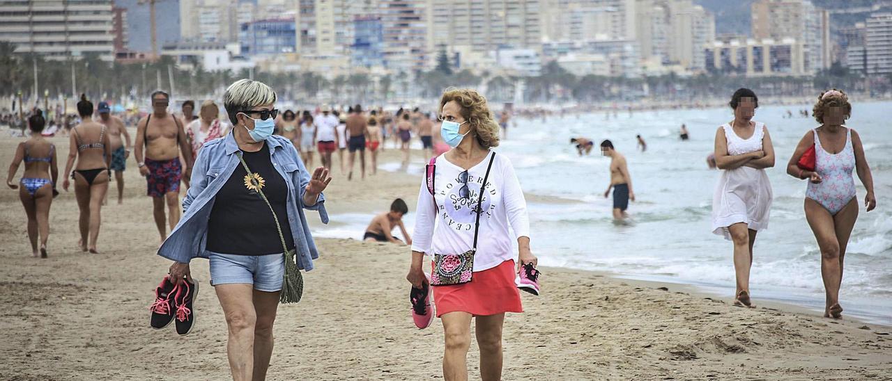 Dos mujeres pasean por la playa de San Juan con mascarilla este lunes en contraste con otras que prescinden de la protección.   PILAR CORTÉS