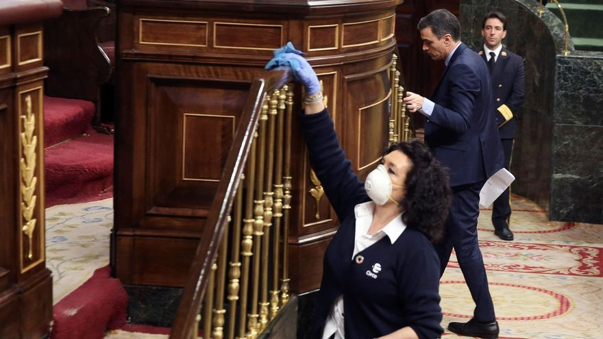 Una trabajadora desinfecta la tribuna del Congreso en el primer Pleno del confinamiento.