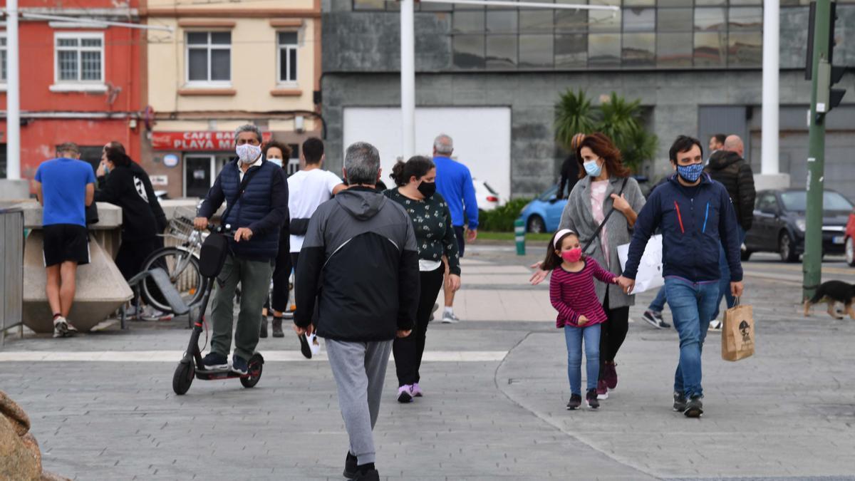 Decenas de personas con mascarilla en el paseo marítimo de A Coruña.