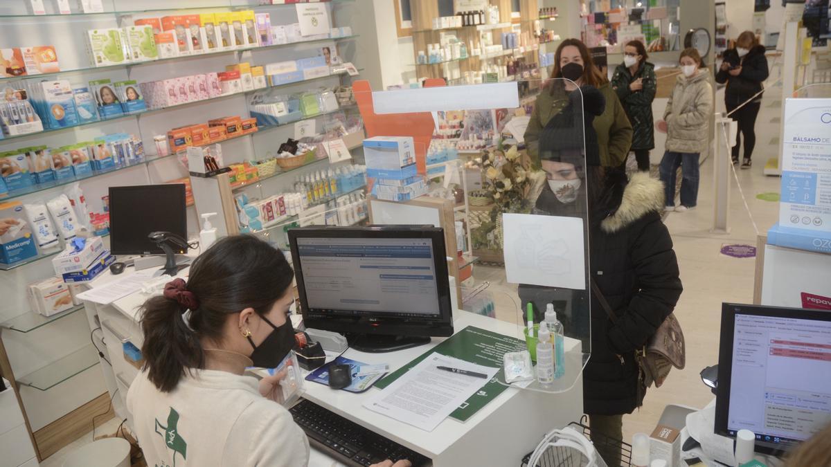 Clientes en una farmacia de Pontevedra que dispensa los test PCR.