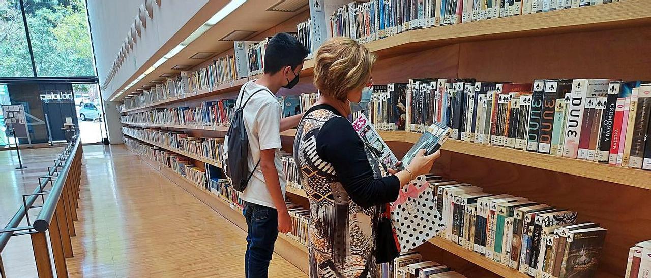 Rosa Beviá busca un volumen par su tío. Abajo, estudiantes en la zona de libros de consulta.  | INFORMACIÓN