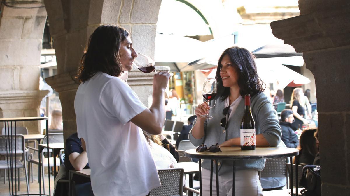 Dos jóvenes disfrutan de un vino en un bar de Ribadavia