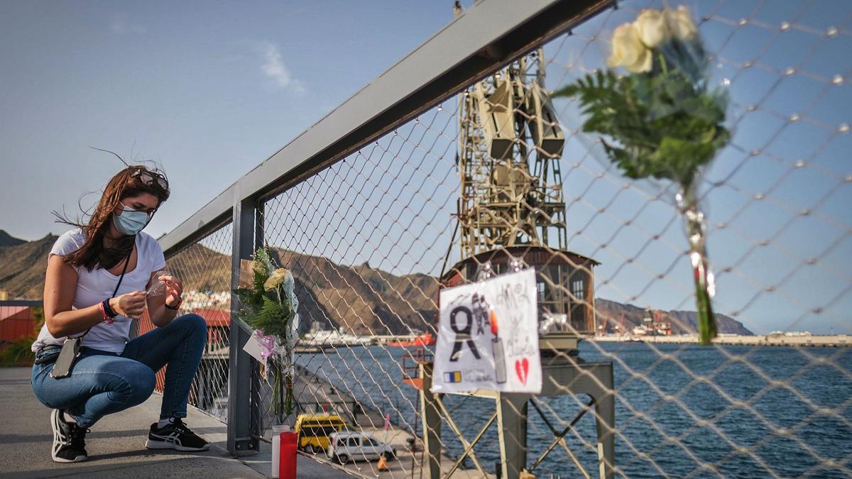 Una mujer deja un recuerdo para Olivia y Anna en el puerto de Santa Cruz de Tenerife. | | ANDRÉS GUTIÉRREZ