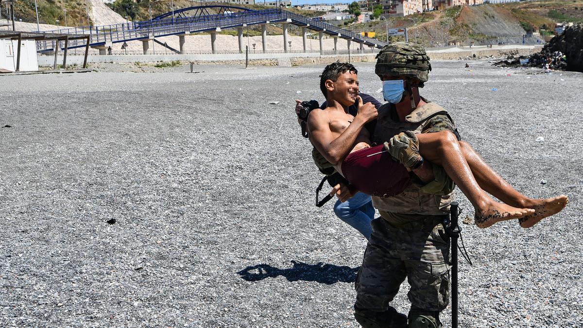 Un miembro del Ejército carga en brazos a un niño marroquí durante la crisis migratoria de Ceuta en mayo
