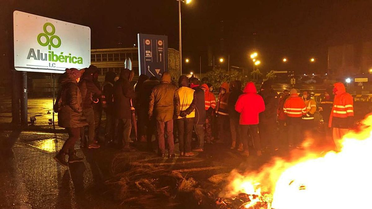 Trabajadores de Alu Ibérica con barricadas en la madrugada de ayer a las puertas de la fábrica. |   // L.O.