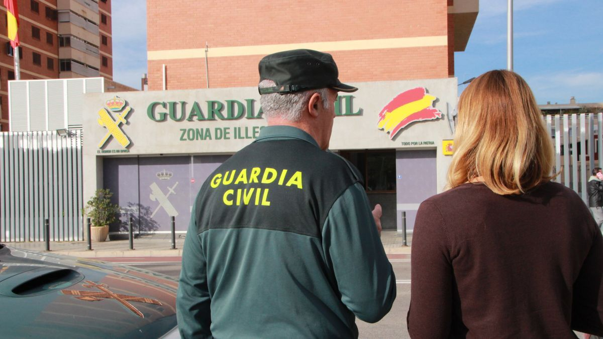 Eine Frau und ein Beamter der Guardia Civil vor dem Polizeihauptquartier in Palma (Archivbild).