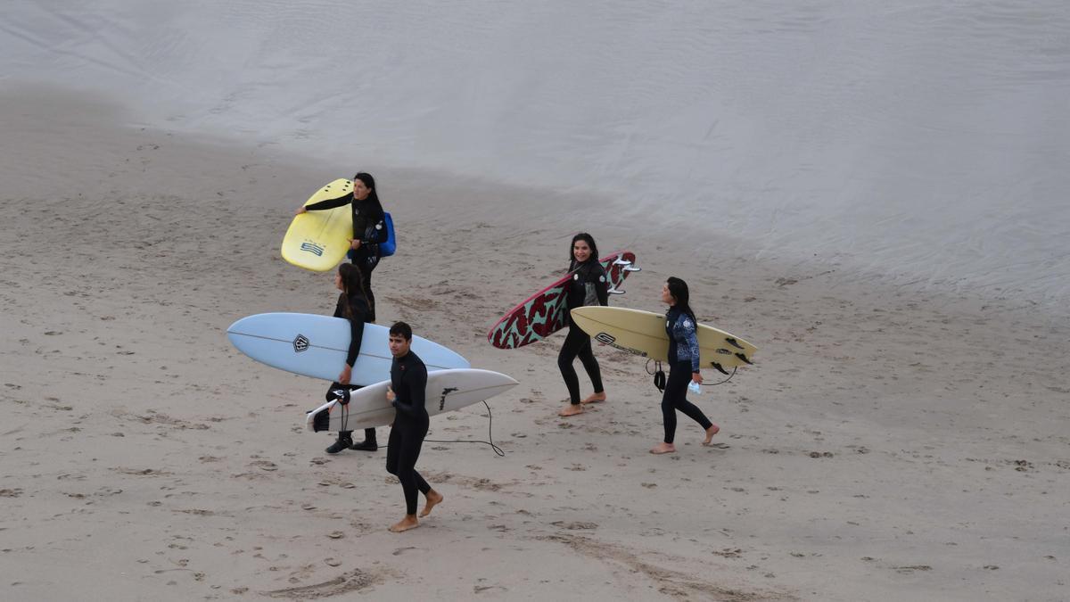 Jóvenes con tablas de surf en la playa.