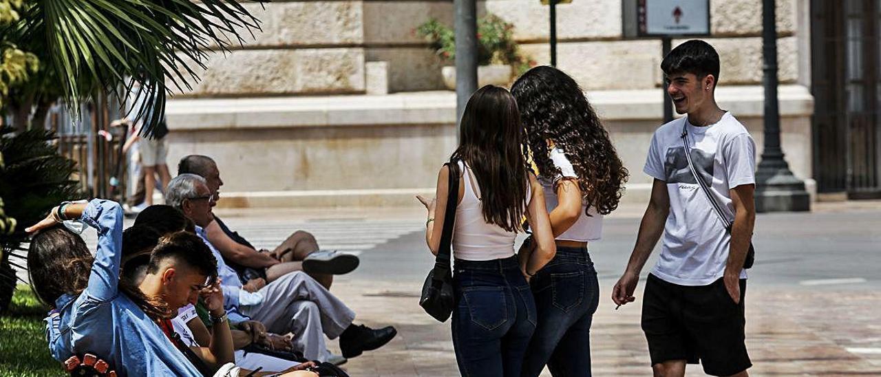 Un grupo de jóvenes, algunos sin mascarilla, hablando en el centro de València.
